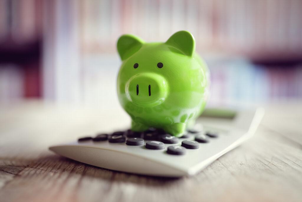 Green piggy bank on top of calculator