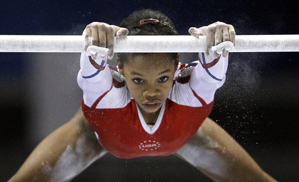 Gabby Douglas swinging from gymnastic bar.
